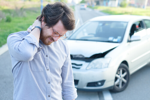 Man holding back of neck in pain in front of crashed car